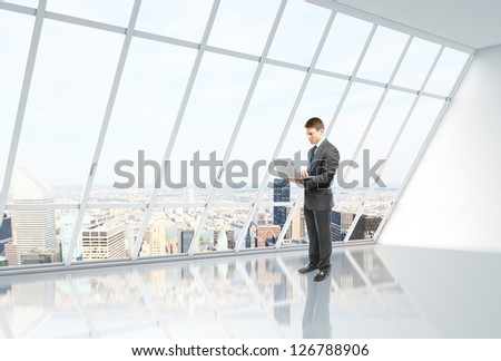 businessman with laptop in white loft office - stock photo