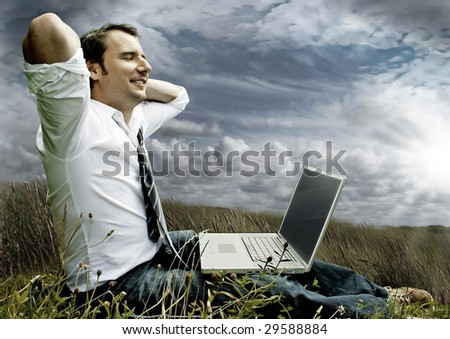 businessman with laptop on a meadow with dark clouds - stock photo