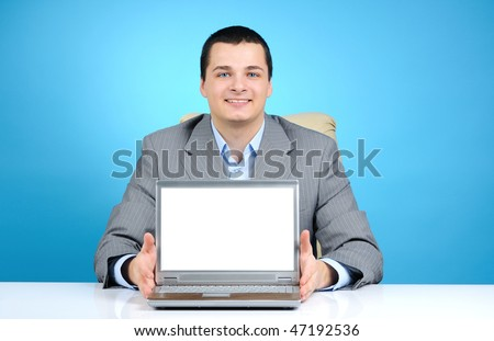Businessman with laptop on blue background - stock photo