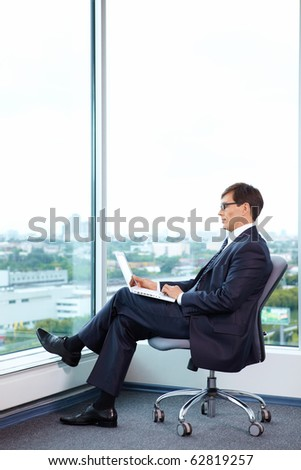 Businessman with laptop on the background of a large window - stock photo