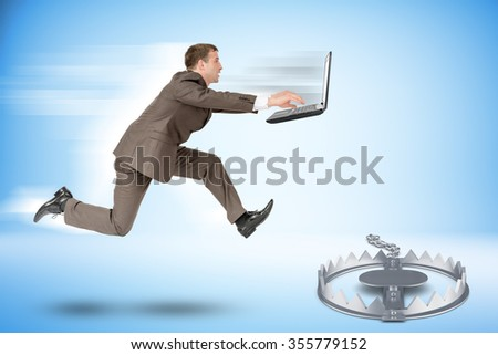 Businessman with laptop running forward to beartrap