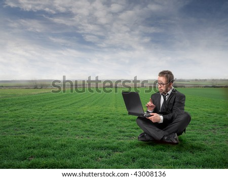 businessman with laptop seated on grass field - stock photo