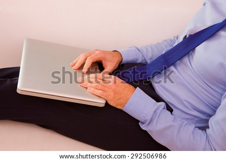 Businessman with laptop sitting couch - stock photo