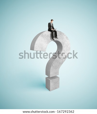 businessman with laptop sitting on question mark