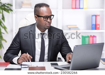 Businessman with laptop. Young African businessman is typing something on laptop in his office. - stock photo