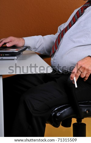 Businessman with large stomach, holding a cigarette working at his desk. Man displays poor eating habits, posture and vices. Can lead to physical problems. - stock photo