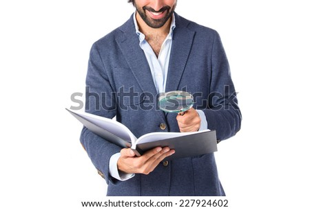 Businessman with loupe reding a book over white background - stock photo