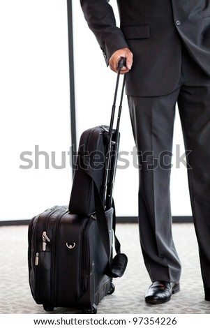 businessman with luggage at airport - stock photo