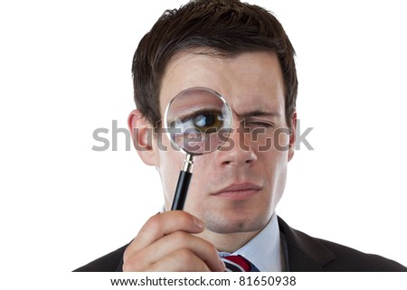 Businessman with magnifying glass in front of his eye. Isolated on white background. - stock photo