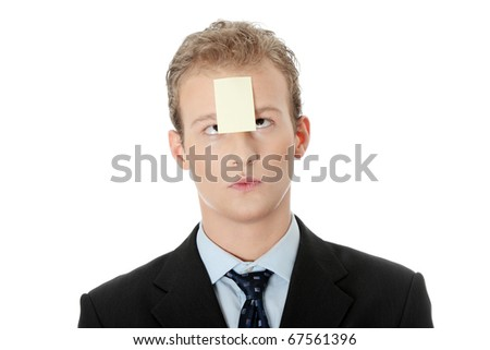 Businessman with memo stock message notes on forehead, over white studio background - stock photo