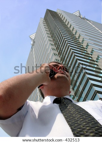 Businessman with mobile phone near a skyscraper-interesting perspective