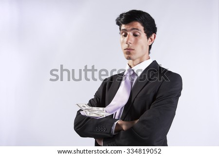 Businessman with money on his flying necktie (isolated on gray) - stock photo