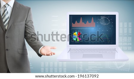 Businessman with open laptop. High-tech graphs at backdrop - stock photo