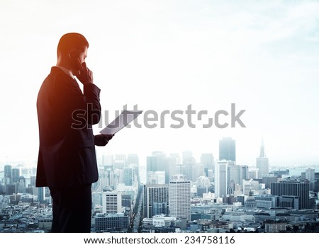 businessman with paper  and  talking on phone - stock photo