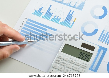 Businessman With Pen Over Graph Doing Calculations - stock photo