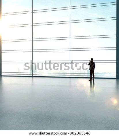 businessman with phone in big sunlight office - stock photo