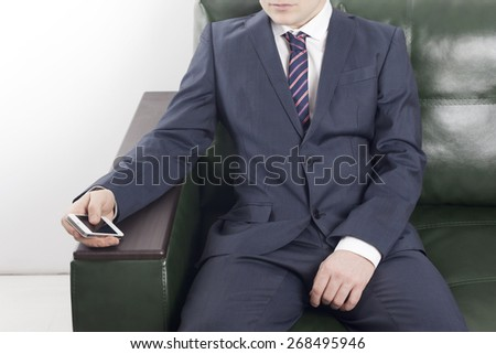 Businessman with phone in hand. Serious pensive young man in a suit sitting on the couch in the office and looking at the phone - stock photo