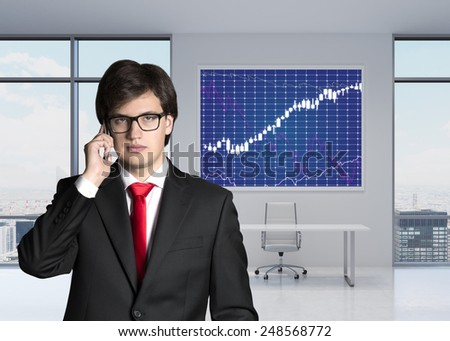 businessman with phone standing in office