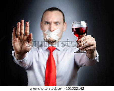 Businessman with plaster on his mouth in red tie holding the glass of red wine and gesturing stop sign by his palm at black background. Represents outcry alcoholic dependency
