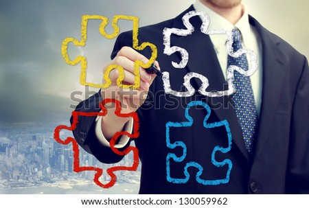 Businessman with puzzle pieces  - concepts of strategy, creativity, and teamwork