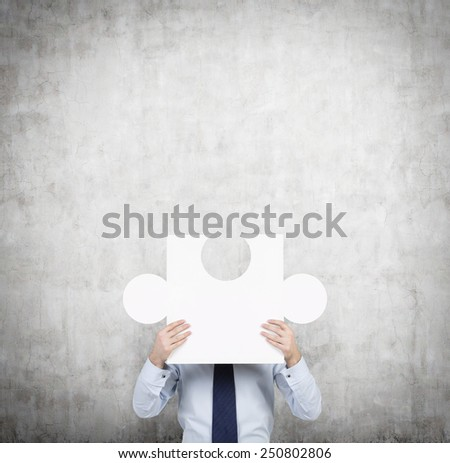 businessman with puzzle standing near concrete wall - stock photo