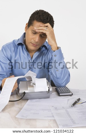 Businessman with severe headache calculating finance - stock photo