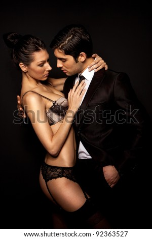 Businessman With Sexy Woman In Lingerie in intimate pose, dark studio portrait on black - stock photo