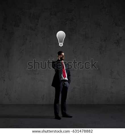 Businessman with smartphone has an idea. Dark and dramatic background. Business, solution, concept.