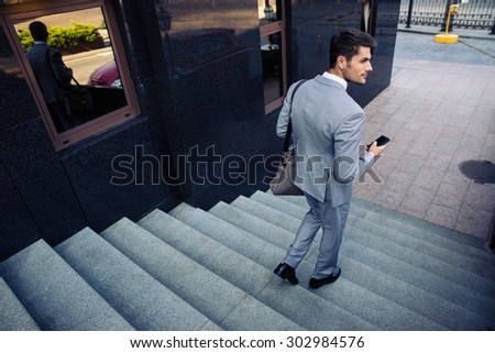 Businessman with smartphone walking on the stairs outdoors and looking  away