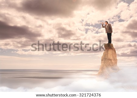businessman with spyglass standing on the top of a mountain - stock photo