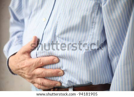 businessman with stomach pain, hands over abdomen - stock photo