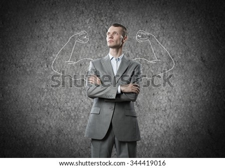 Businessman with strong arms drawn with chalk behind his back - stock photo