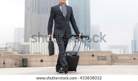 businessman with suitcase walking on road - stock photo
