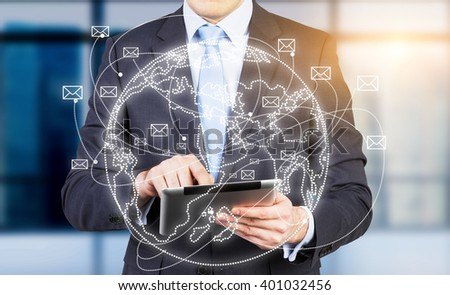 Businessman with tablet, globe with envelopes flying around in front of him. Concept of communication. - stock photo