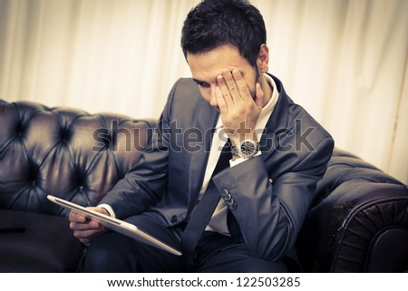 Businessman with tablet on a sofa