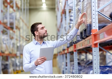 businessman with tablet pc at warehouse - stock photo