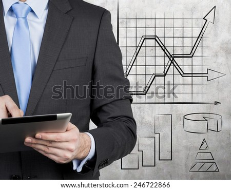 businessman with touch pad and drawing graphs on wall - stock photo