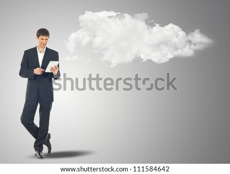 Businessman with touch screen Internet Tablet and the clouds. Maybe will used as concept cloud service - stock photo