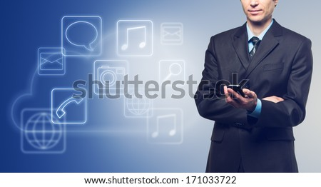 Businessman with touch screen phone and the cloud with applications icons on blue background - stock photo