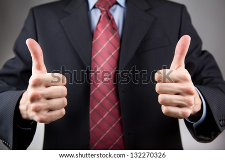 Businessman with two thumbs up. Neutral background - stock photo
