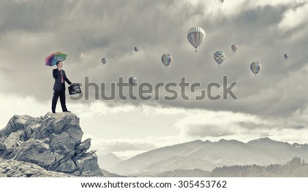 Businessman with umbrella and suitcase standing on mountain top - stock photo