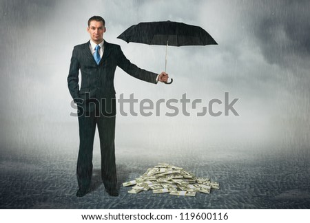 Businessman with umbrella stands at cloudy background and protects a money. Financial safety