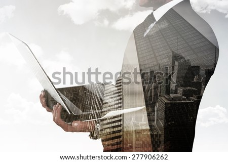 Businessman with watch using tablet pc against low angle view of skyscrapers - stock photo
