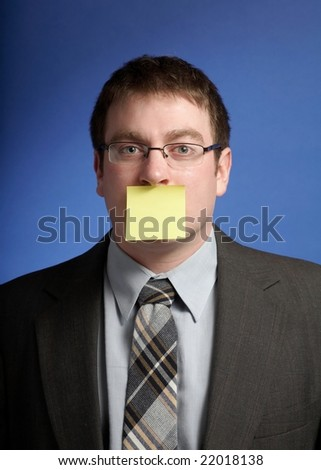Businessman with yellow sticky pad over mouth - stock photo