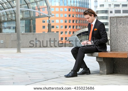 businessman working at a laptop sitting in the city park - stock photo