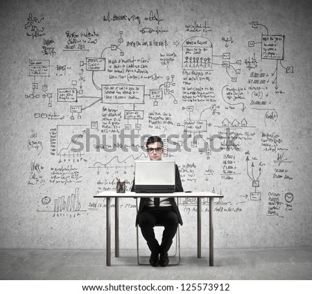 Businessman working at a laptop with in the background a wall full of economy drawings - stock photo