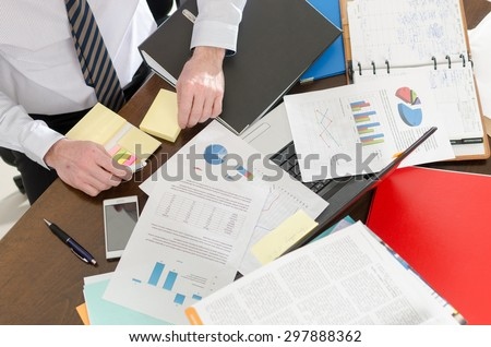 Businessman working at a untidy and cluttered desk - stock photo