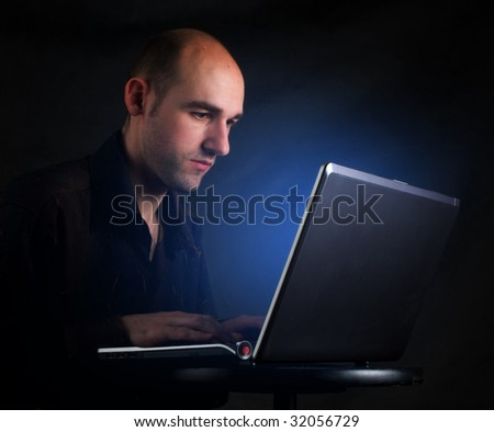 Businessman working at computer laptop in night - stock photo