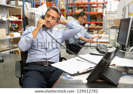 Businessman Working At Desk In Warehouse - stock photo