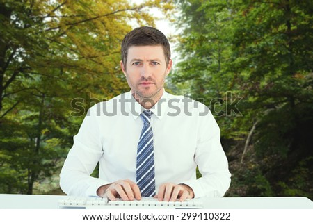 Businessman working at his desk against scenic shot of narrow road along forest - stock photo